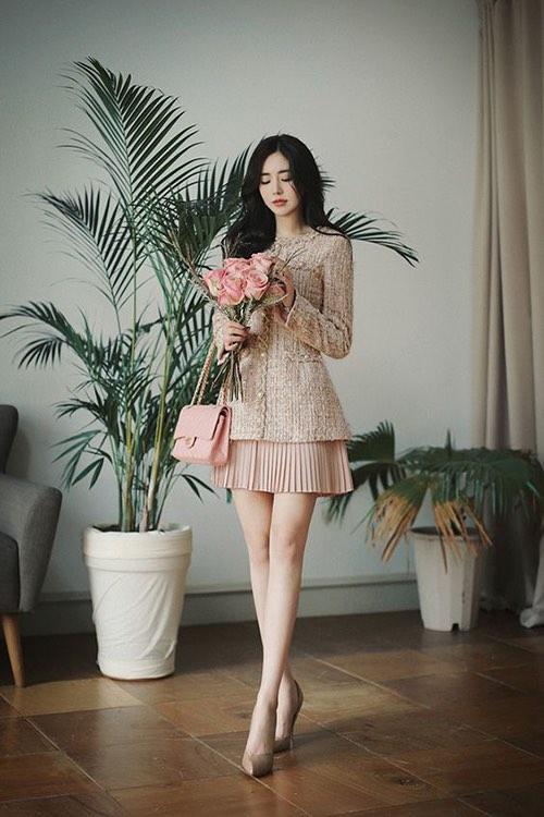 Set đồ phối hợp ăn ý giữa tông hồng pastel, hồng nude cho áo vải tweed, chân váy xếp ly, túi xách tay và giày cao gót tôn dáng hiệu quả.