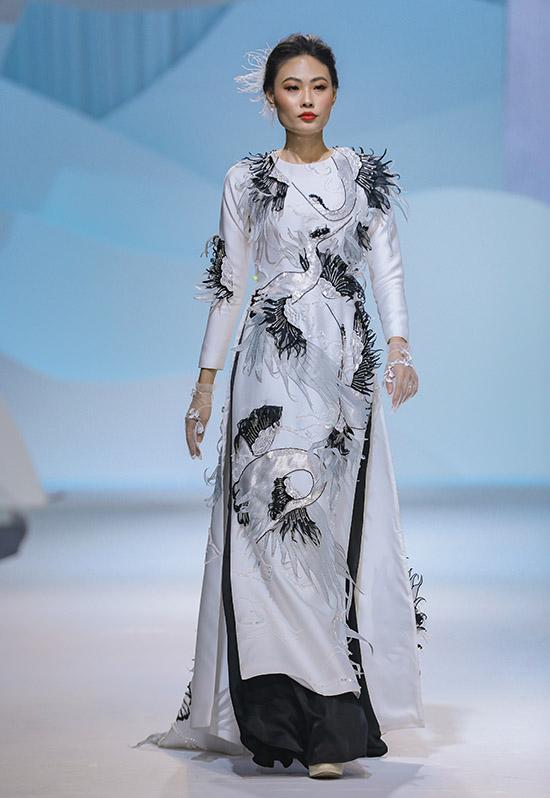 Chân dài Mai Giang sải bước trong trang phục hai màu đen trắng, thêu hình chim phượng hoàng bay lượn.
