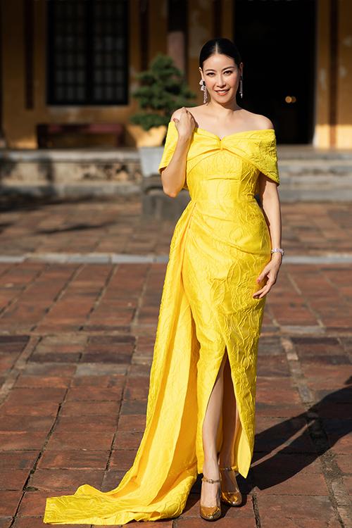 Hà Kiều Anh khoe nét sang trọng và quyến rũ trong mẫu đầm trễ vai thiết kế trên vải gấm tông vàng nổi bật.