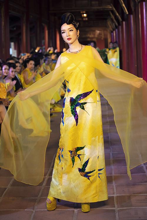 Hoa hậu Giáng My khoe dáng với trang phục kết hợp vải gấm, lụa và trang trí hoạ tiết chim én thêu - đính kết nổi tỉ mỉ.
