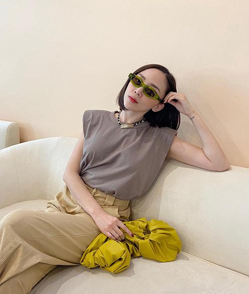 Áo thun độn vai, kiểu sát nách được Tóc Tiên mix cùng quần lưng cao màu trung tính. Phụ kiện đi kèm là kính mini và clutch tông xanh - vàng bắt mắt.