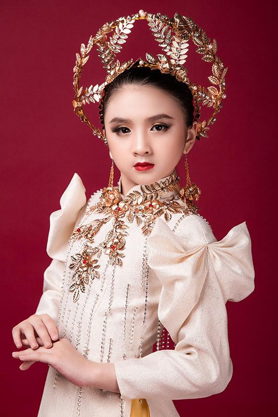 Cô bé 9 tuổi khoe vẻ đáng yêu với áo dài lấy cảm hứng hình ảnh nữ thần ánh sáng trong thần thoại Hy Lạp. Trang phục có điểm nhấn là các hoạ tiết nổi bằng kim loại cùng chiếc mấn độc đáo.