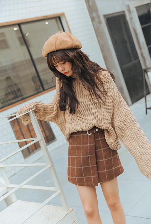 Những cô nàng dáng mảnh và muốn thể hiện sự phá cách với trang phục thu đông có thể tham khảo cách mix áo len dáng rộng cùng chân váy vải tweed.