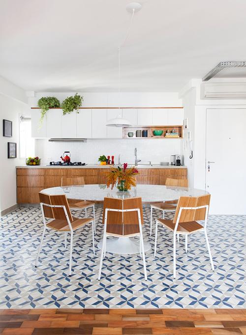Bàn ăn làm bằng đá cẩm thạch, ghế gỗ tạo sự liên kết với nội thất tủ bếp, sàn gỗ lát phòng khách.