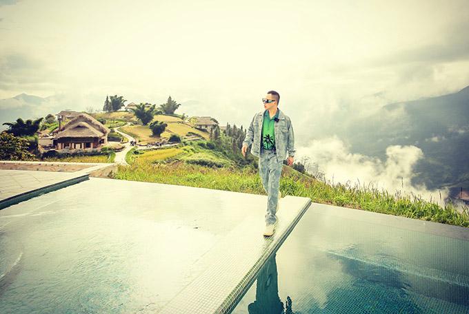 Vũ Khắc Tiệp diện trang phục sành điệu, cá tính tạo dáng trên hồ bơi một khách sạn nổi tiếng ở Sapa. Từ vị trí này, anh ngắm được cảnh thiên nhiên mây trời hùng vĩ, những mái nhà đơn sơ của người dân tộc nằm cheo leo trên triền đồi.