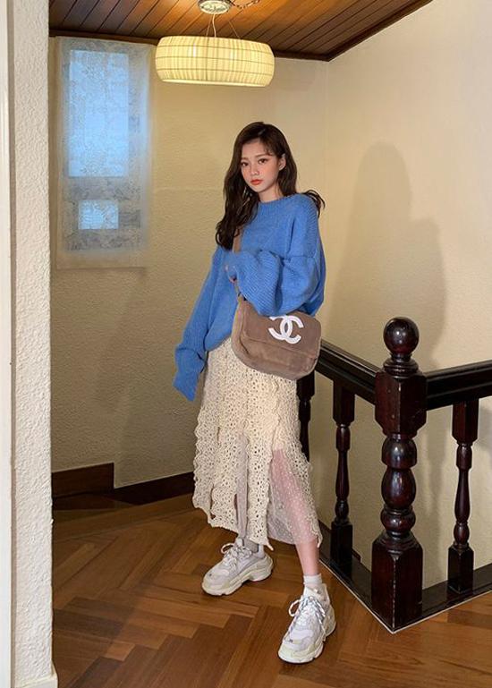 Áo len cổ lọ tông xanh dương cùng chân váy vải ren trắng mang tới nét hài hòa cho tổng thể. Phụ kiện đi kèm là túi đeo chéo và giày sneaker.