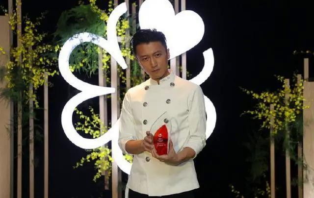 Tạ Đình Phong cầm chiếc kỷ niệm chương của Michelin Guide.