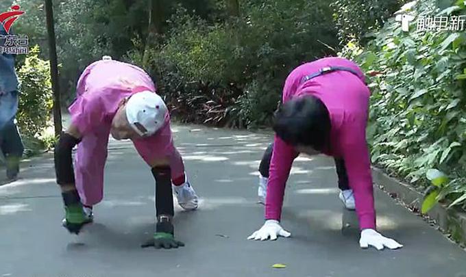 Cụ Li (trái) và một trong những người nhóm cụ đang thực hiện động tác bò trong công viên. Ảnh: Guangdong Television.
