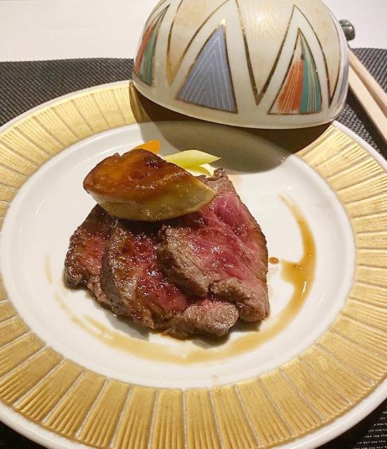 Món hoa hậu của bàn tiệc là bò wagyu A5 hảo hạng nướng than. Thịt bò được lấy từ vùng Kurobe - một trong những địa phương nổi tiếng với công nghệ chăm sóc và sản xuất thịt bò wagyu ở Nhật. Vị thịt ngọt, thơm, mịn, có hàm lượng chất béo, được mô tả là mỗi miếng cắn đều khiến người sành ăn mê mẩn. Tại nhà hàng này, đầu bếp nướng trên lửa rơm, tạo ra mùi thơm độc đáo, hòa quyện của khói rơm, nhiệt độ tự nhiên làm vị thịt đậm đà hơn.