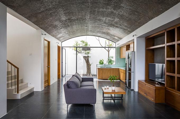 Không gian vòm lớn được kết nối với một vòm khác, gồm bếp, phòng khách thông qua cửa xếp. Nhà có phòng khách tối giản.