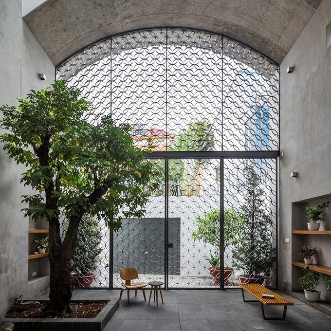 Khoảng không gian ngoài trời này được ngăn cách với bên ngoài chỉ bằng một tấm lưới thép, giúp yếu tố tự nhiên như ánh sáng, mưa và gió tiếp cận vào nhà.