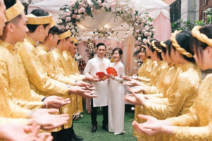 Hai vợ chồng Thủy Tiên - Thế Anh mặc áo dài cặp, cùng phát phong bao cho đội bê tráp.