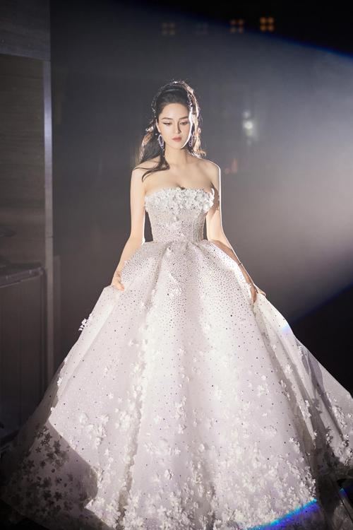Mẫu đầm mà á hậu diện có tên gọi Olivin, được tạo nên bởi 50.000 viên pha lê Swarovski, 10.000 cánh hoa được làm thủ công. Chiếc váy được NTK gửi gắm ý nghĩa ở nơi đâu có tình yêu, ở đó có sức sống mãnh liệt.