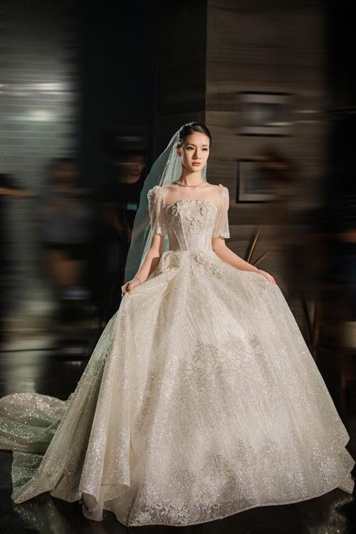 Mẫu đầm cưới được dựng phom corset, giúp siết chặt eo thon, vải váy lấp lánh, họa tiết được thêu, đính bởi chỉ thêu bắt sáng nhập khẩu.