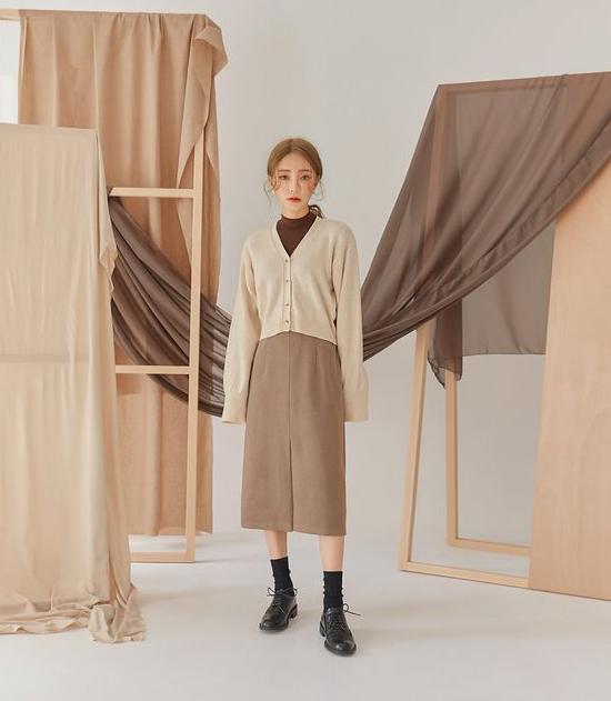 Set trang phục cho nàng mê màu trung tính với cách mix layer gồm áo cổ trụ, cardigan dáng lửng và chân váy midi. Giày da hoặc bốt cổ thấp sẽ là phụ kiện mang tới tổng thể hài hòa.