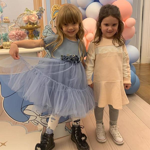 Cô nhóc mặc váy xanh, hồn nhiên, đáng yêu trong bữa tiệc sinh nhật ngọt ngào.