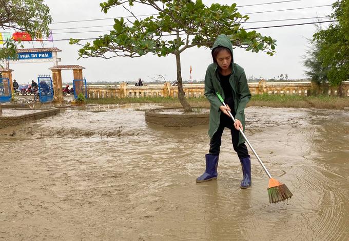 Vợ anh - Minh Hà - cũng tất bật quét bùn trong sân trường Tiểu học Thuận Hòa, huyện Hương Trà, Huế. Đây là nơi tránh bão, lũ của bà con địa phương mỗi khi có thiên tai. Hiệu trưởng của trường cho biết đây là vùng trũng nên năm nào cũng bị ngập sâu.