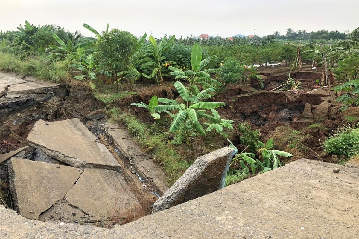 Đường bê tông bị sụt, sâu buộc nhà chức trách phải đổ đất đá, căng dây phong tỏa 2 đầu đường, nhằm ngăn không cho người dân và các phương tiện qua lại để bảo đảm an toàn. Ảnh: Giang Chinh
