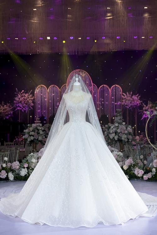 Chất liệu được sử dụng để làm váy là vải metallic tulle. Sự đắt giá của mẫu đầm nằm ở 1.500 viên pha lê Czech kèm ngọc trai nhân tạo được đính dọc thân, giúp tăng độ bắt sáng tối đa với khả năng tán sắc khác nhau dưới ánh đèn sân khấu.  Lúp cưới được thiết kế riêng cho bộ cánh này, tôn nét đẹp của cô dâu Thủy Tiên.
