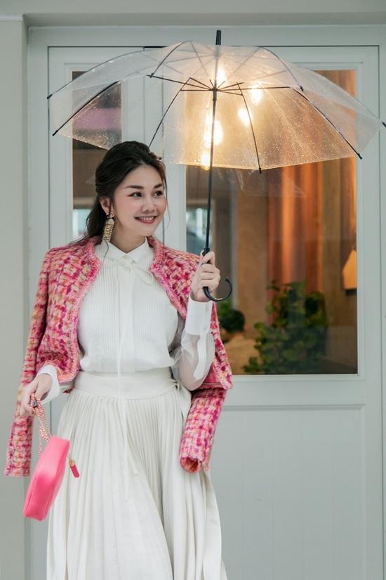Váy trắng thoạt nhìn đơn giản, nhàm chán được Thanh Hằng tô điểm bằng áo khoác vải tweed sang trọng. Sắc hồng ngọt ngào cũng giúp nữ siêu mẫu thêm thu hút ánh nhìn.