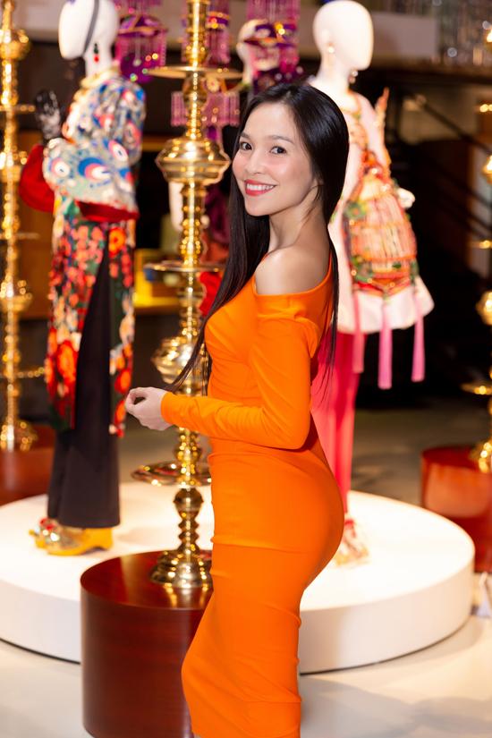Ca sĩ Hiền Thục tôn đường cong với váy ôm khít eo trên tông màu cam nổi bật.