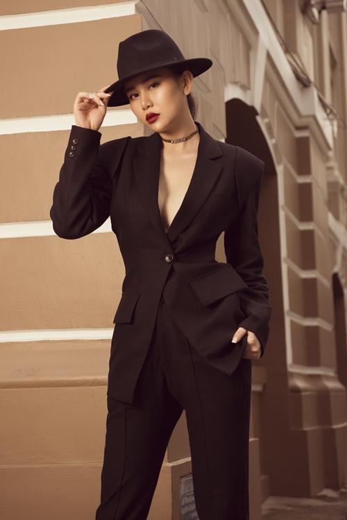 Mũ fedora giúp Cao Thùy Trang trông cá tính. Cô diện mốt không nội y để bộ suit đen dù nam tính vẫn toát lên sự sexy nhờ vòng một lấp ló.