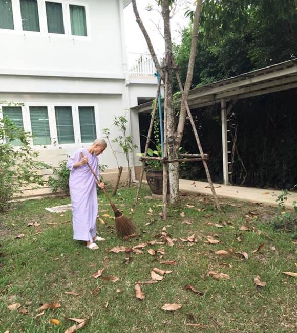 Bà Srirasmi Suwadee mặc áo ni cô quét dọn trong khuôn viên chùa. Ảnh:Twitter.