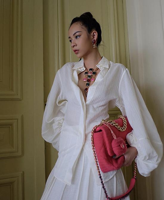 Diện sơ mi đồng điệu sắc trắng với chân váy midi nhưng Phí Phương Anh vẫn giúp mình trở nên cá tính bởi bộ phụ kiện vòng cổ to bản và túi Chanel gam hồng bắt mắt.