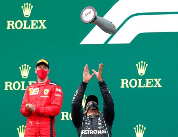Hamilton tung Cup mừng chiến thắng trước mặt đối thủ Vettel. Tay đua người Đức của đội Ferrari cũng đã 4 lần vô địch thế giới và từng cạnh tranh quyết liệt với Hamilton những năm trước.