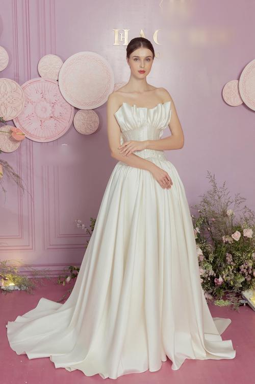 Mẫu đầm số 1 có thể lọt vào tầm ngắm của cô dâu Viên Minh là chiếc váy thuộc top 10 đầm tối giản bán chạy của thương hiệu. Váy được làm từ lụa mikado cao cấp, giúp tôn dáng tối đa, phần thân trên của váy được tạo hình giống đóa hoa đang hé nở trong nắng sớm mai. Phần eo được siết nhờ định hình theo phom dáng corset.