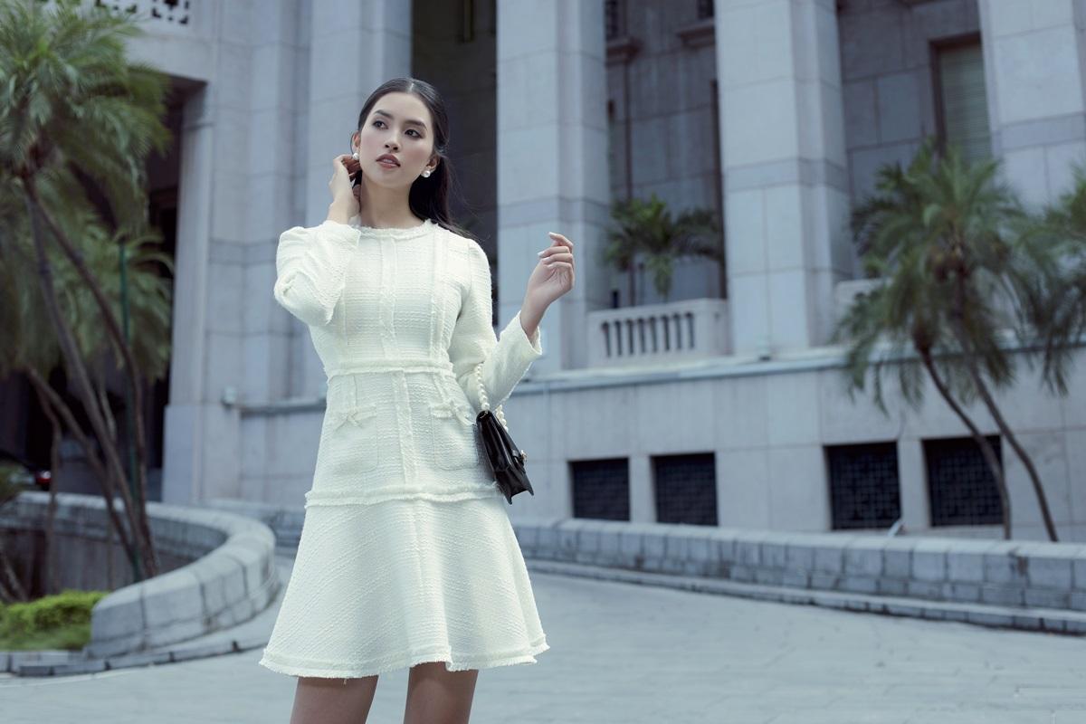 Bộ ảnh của Tiểu Vy tiếp nối chuỗi runway Living in the city mừng 15 năm phát triển của IVY moda. Cô diện đầm vải tweed gam trắng nhấn vào những đường diềm dọc thân, phối cùng túi cầm tay gam đen.