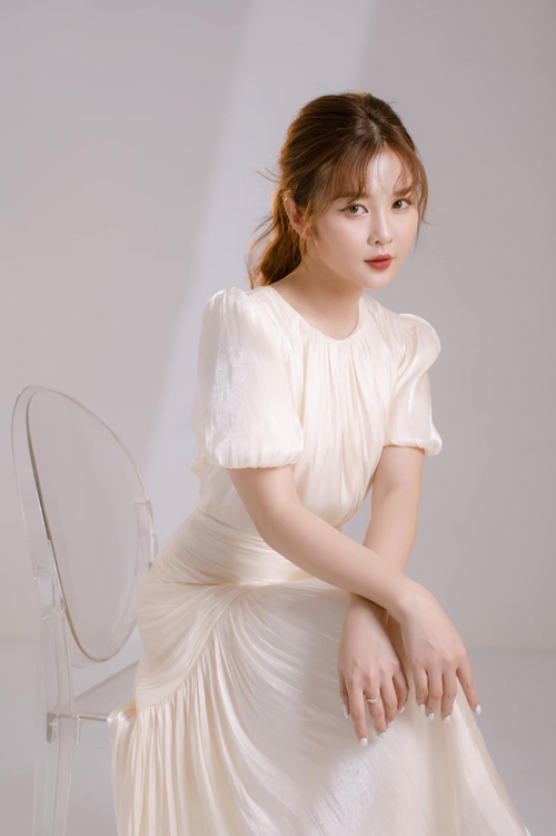 Váy Viên Minh chọn diện là phiên bản màu kem sữa, chất liệu flash satin, bóng nhẹ, mềm mại và đặc tính không nhăn, phù hợp khi chụp ảnh cưới ngoài trời, không tốn công là ủi, dễ gấp gọn trong vali.