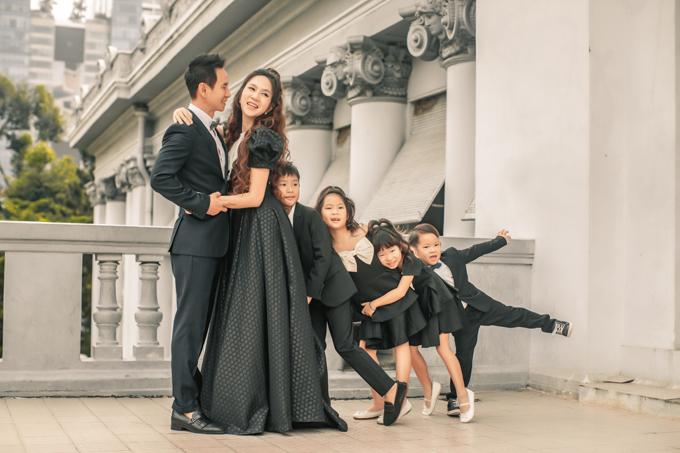 Cặp vợ chồng cùng các con chụp hình ở bảo tàng TP HCM. Các em bé tạo hình lí lắc bên cha mẹ.