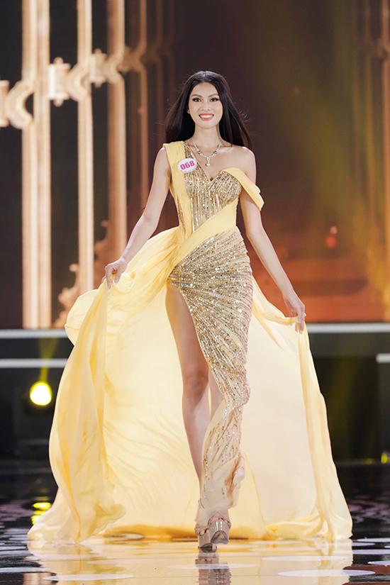 Á hậu 2 Nguyễn Lê Ngọc Thảo lộng lẫy với đầm vàng nhạt đính sequins với phom dáng bất đối xứng. Cô cao 1,74 m, số đo ba vòng 81-61-95 cm.