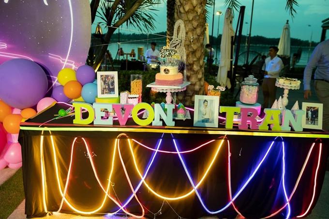Bàn tiệc sinh nhật được trang hoàng với bánh kem, bóng bay, những tấm ảnh chụp riêng của Devon và những bức ảnh Devon chụp cùng bố Sơn, mẹ Ánh.