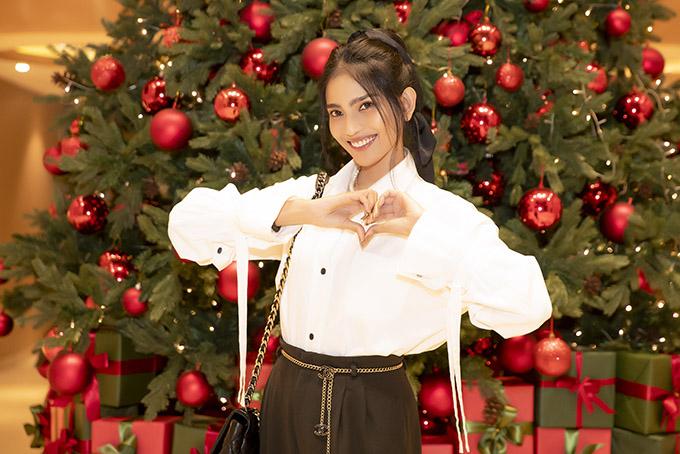 Á hậu các dân tộc Việt Nam 2007 trông trẻ trung, rạng rỡ khi mặc kín đáo, thanh lịch. Cô hào hứng chụp ảnh với cây thông Noel rực rỡ trang trí tại một khách sạn.