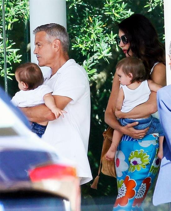 Vợ chồng George Clooney bế cặp song sinh.
