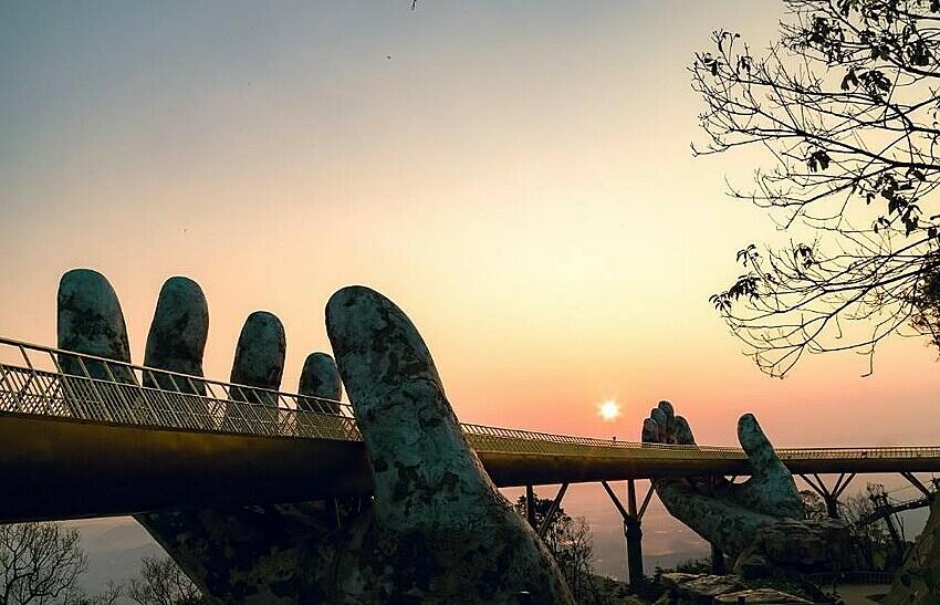 Bình minh ló rạng, chân mây vừa ửng hồng, nền trời mơ màng phủ lên cây cầu một màn sương dịu dàng, huyền ảo, Cầu Vàng mang một vẻ đẹp lãng mạn, siêu thực. Để bắt được khoảnh khắc sớm mai trên Cầu Vàng, bạn nên nghỉ đêm tại khách sạn trên đỉnh Bà Nà và dậy thật sớm đón bình minh dần ló rạng trên cây cầu.
