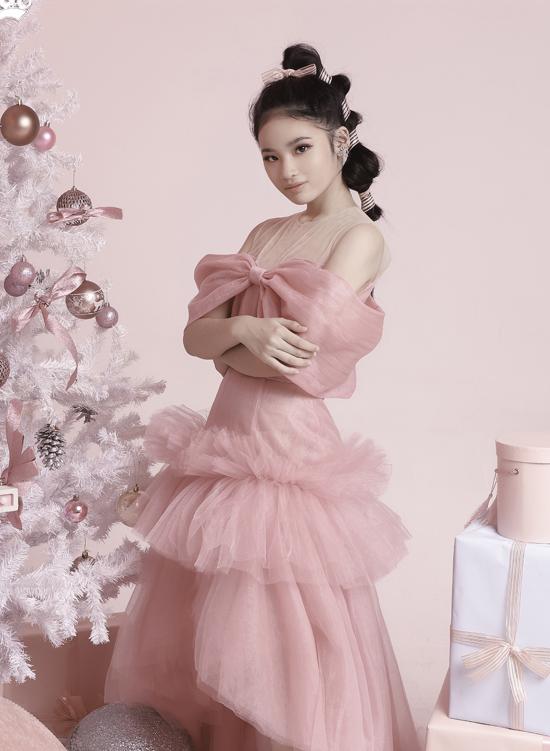 Bé hóa thân nàng công chúa xinh đẹp với váy voan hồng xếp tầng tạo dáng bên cây thông Noel.