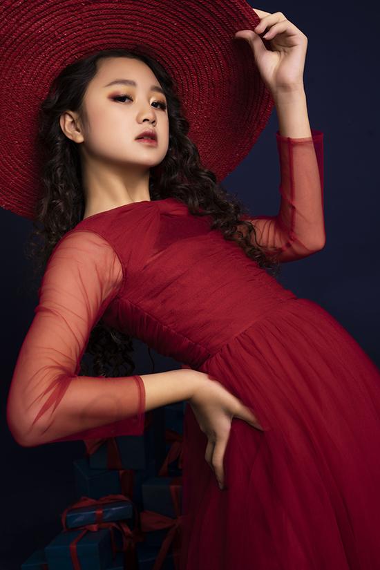 Mái tóc xoăn lọn nhỏ cùng kiểu trang điểm tông cam đỏ khiến mẫu nhí trông cá tính hơn khi diện váy bánh bèo. Mới 11 tuổi nhưng Kim Chi luôn thể hiện biểu cảm đa dạng khi chụp ảnh hoặc diễn catwalk.