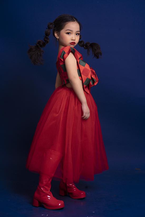 Mẫu nhí Bảo Trang phối chân váy ren đỏ với crop-top kẻ đính nơ màu đồng điệu. Set đồ trở nên cá tính hơn khi được kết hợp với boot da bóng và kiểu tóc hai bên.