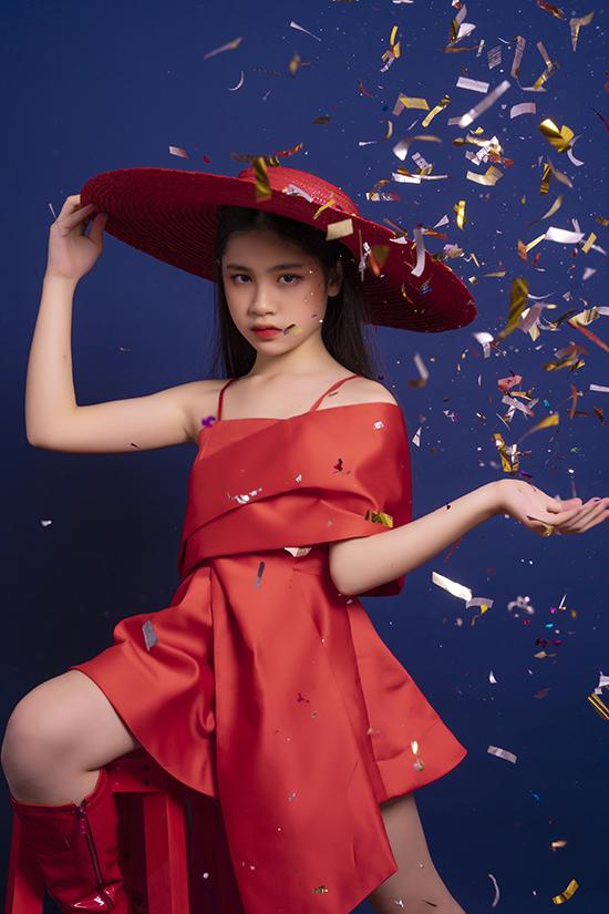 Mẫu nhí Thủy Tiên chọn phong cách điệu đà khi diện váy xếp nếp màu đỏ rực.