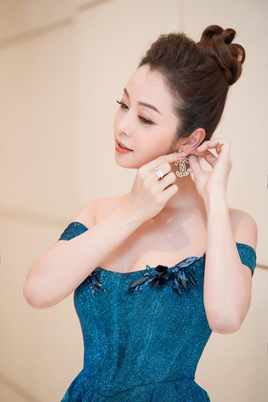 Cô phối váy dạ hội với khuyên tai Chanel to bản và mái tóc búi cao khoe toàn bộ gương mặt thanh tú.